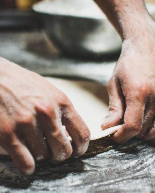 mehlige Hände, die einen Teig auflegen