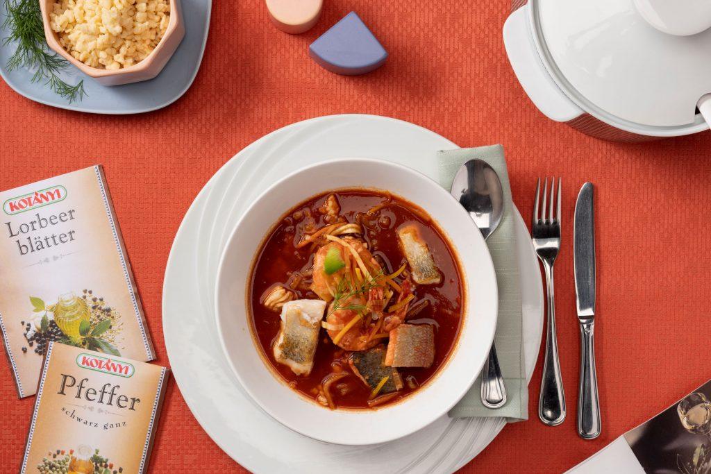 Рыба и морепродукты в бульоне с паприкой, рядом лежат пакетики лаврового листа и перца.
