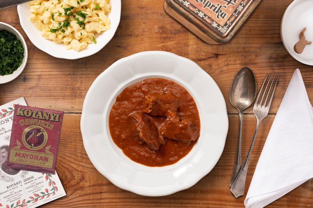 Наполненная гуляшом тарелка и небольшая тарелка шпецле на темном деревянном столе.