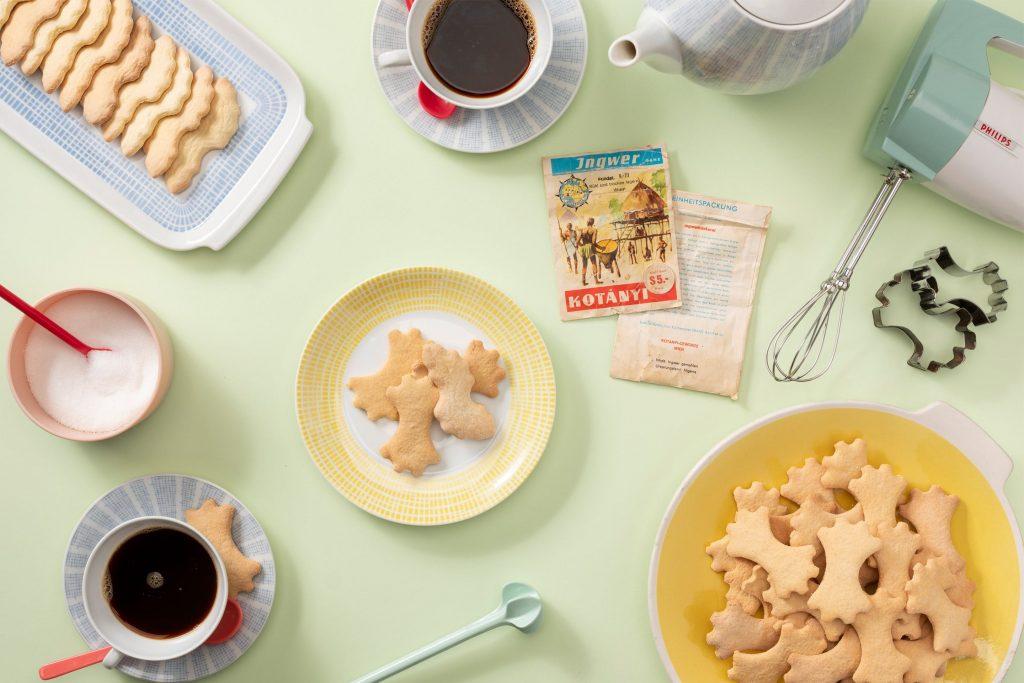 Имбирное печенье на десертной тарелке и пастельный кофейный сервиз.