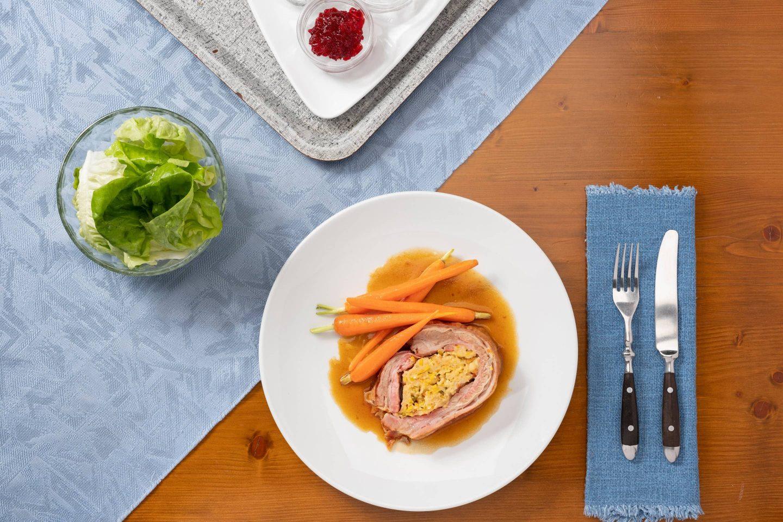 Две порции фаршированной телячьей грудинки с глазированной морковью на белой тарелке.