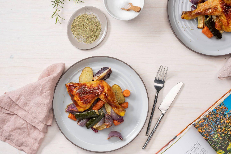 Курица с розмарином и жареными овощами рядом с современной упаковкой розмарина.