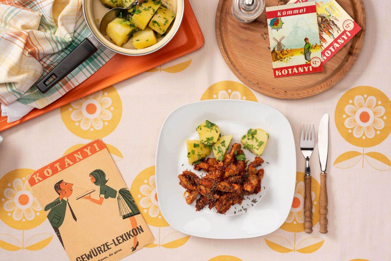 Порция свинины с тмином и картофеля с петрушкой на квадратной тарелке с закругленными краями.