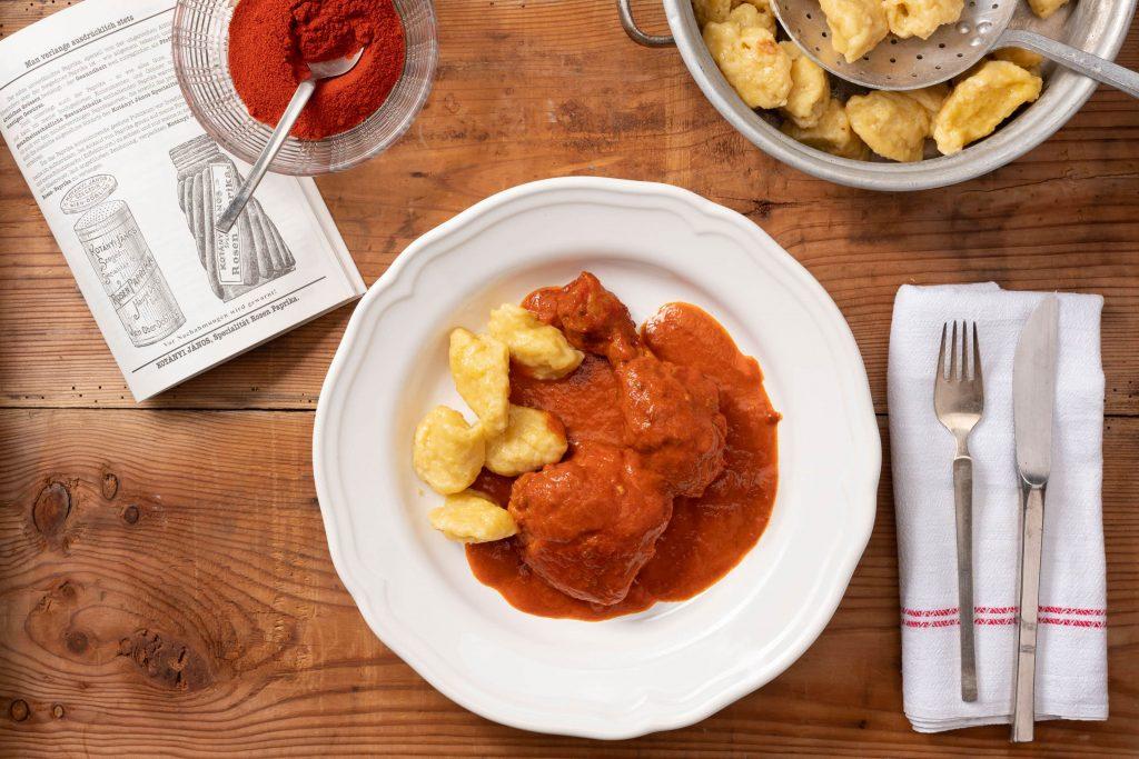 Глубокая тарелка с курицей с паприкой и клецками, рядом стоит миска с молотой паприкой.