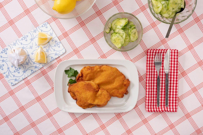 Два венских шницеля с салатом из огурца, украшенным укропом.