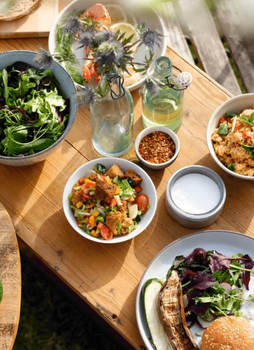 На столе расставлены различные салаты.
